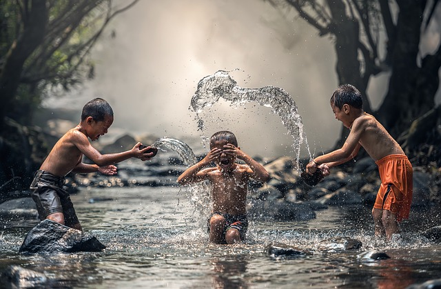 3 Kinder spielen im Wasser