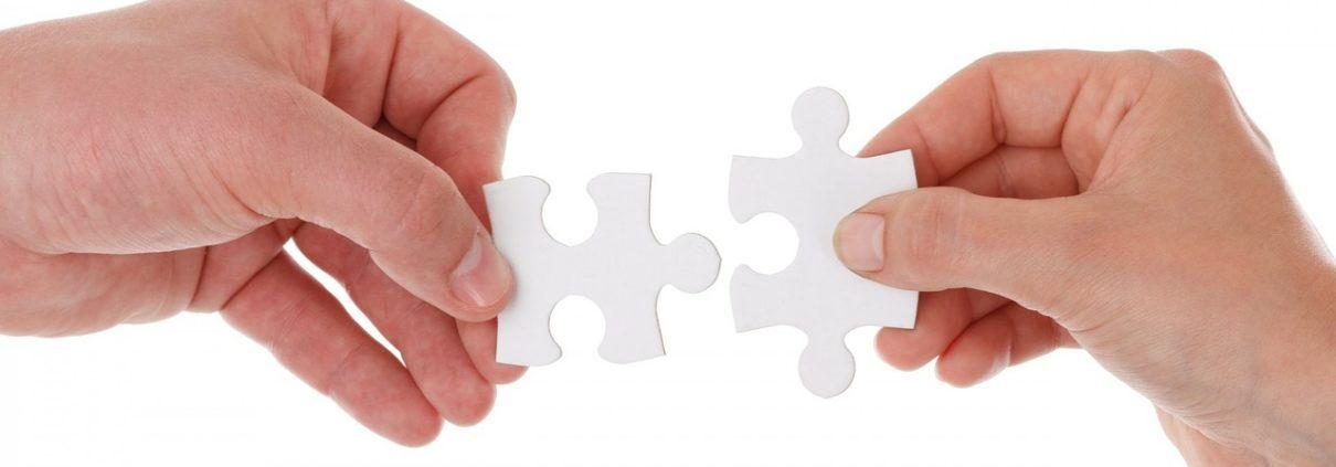 2 Hände strecken sich passende Puzzleteile entgegen