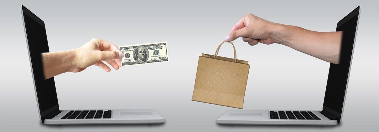Hand mit Geldschein und Hand mit Einkaufstüte