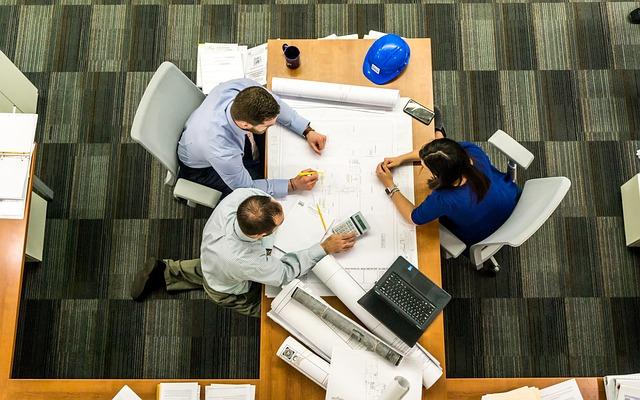 3 Personen sitzen an Tisch und arbeiten